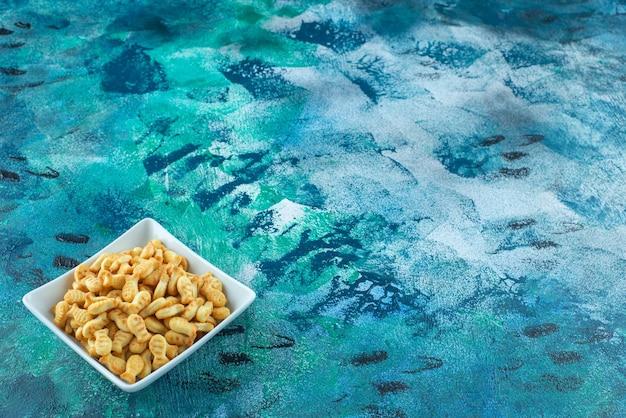 Chrupiąca ryba krakersa w misce, na niebieskim stole.
