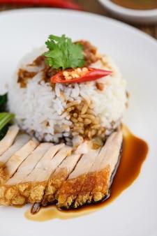 Chrupiąca wieprzowina na białym talerzu zwieńczonym sosem i chili podzielonym na pół.
