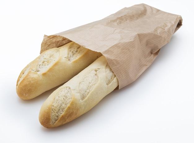 Chrupiące bochenki świeżo upieczonego białego chleba w papierowej torebce. odosobniony.