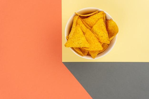 Chrupiące chipsy kukurydziane tortilla nachos w białym talerzu z miejscem na obturację tekstu.
