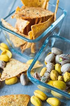 Chrupiące chipsy nachos i pistacje orzechy słone i żółte z szafranem, przekąski w kwadratowych szklanych talerzach