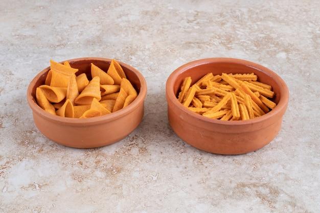 Chrupiące chipsy w rożku i grzanki w miseczkach na marmurowym stole.