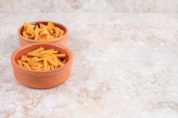 Chrupiące chipsy w rożku i grzanki w miseczkach, na marmurze.