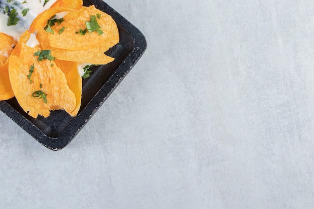 Chrupiące chipsy wraz z majonezem na czarnej desce do krojenia.