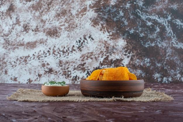 Chrupiące chipsy ziemniaczane i jogurt w talerzach na fakturze, na marmurowym stole.