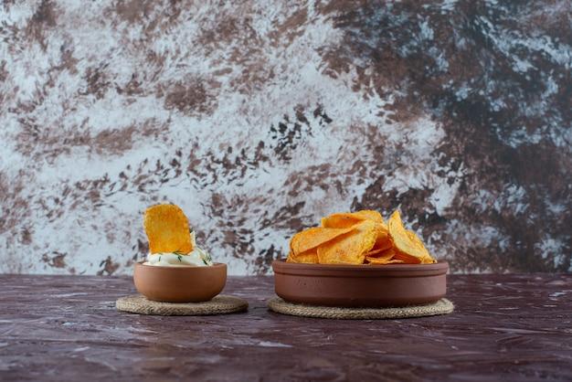Chrupiące chipsy ziemniaczane i jogurt w talerzach na podstawkach, na marmurowym stole.