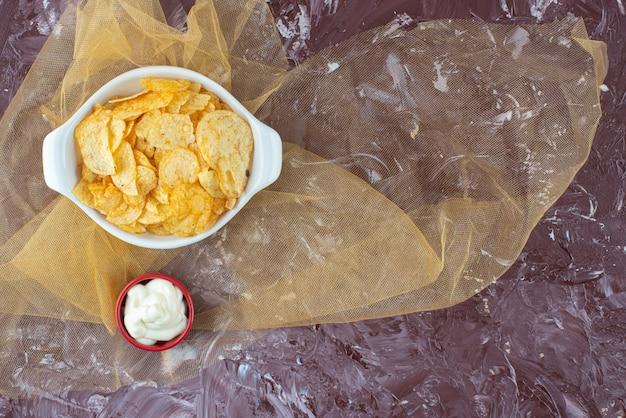 Chrupiące chipsy ziemniaczane i jogurt w talerzach na tiulu, na marmurowym stole.