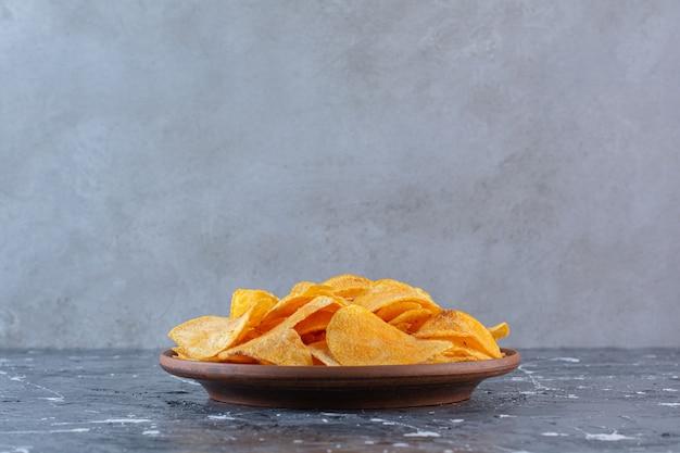 Chrupiące chipsy ziemniaczane w talerzu, na marmurowej powierzchni