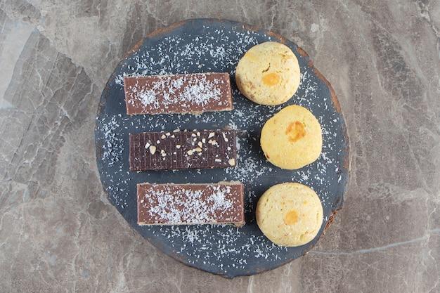 Chrupiące gofry czekoladowe i kruche ciasteczka na pokładzie na marmurze.