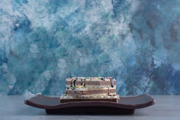 Chrupiące gofry waniliowe ozdobione posypką na ciemnym talerzu.