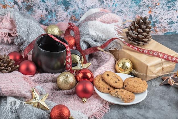 Chrupiące imbirowe ciasteczka w białym spodku z filiżanką napoju i świątecznymi ozdobami wokół
