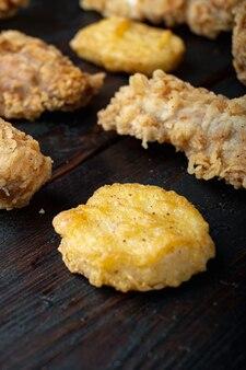 Chrupiące kawałki kurczaka smażone kentucky na ciemnym drewnianym stole.