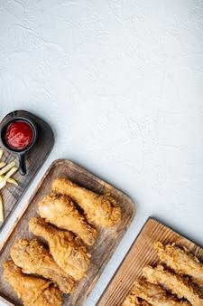 Chrupiące kawałki kurczaka smażone po kentucky na białym stole, leżak na płasko.
