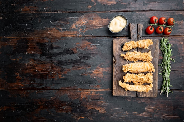 Chrupiące kawałki pieczonego kurczaka na starym ciemnym drewnianym stole, leżak na płasko, z miejscem na kopię.