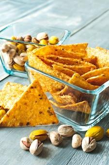 Chrupiące nachos i pistacje słone i żółte z szafranem, przekąski w kwadratowych szklanych talerzach