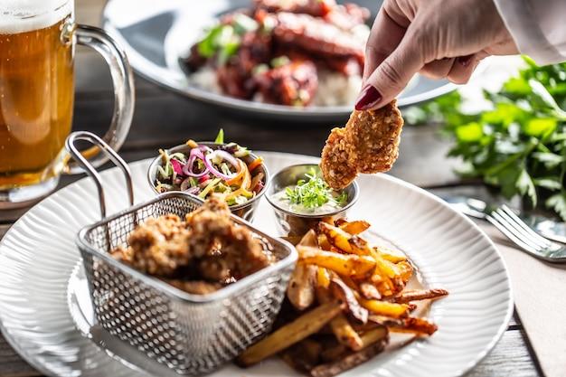 Chrupiące panierowane nuggetsy z kurczaka z frytkami podawane na talerzu z dipem i surówką.