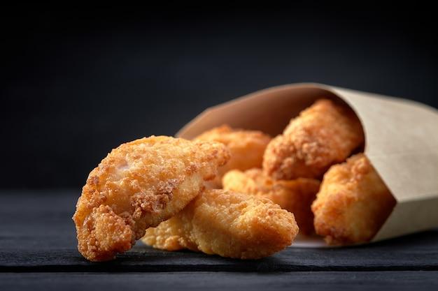 Chrupiące paski kurczaka w papierowym pudełku na ciemnym tle. koncepcja fast foodów śmieci. selektywne ustawianie ostrości. skopiuj miejsce na tekst