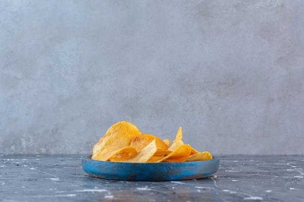 Chrupiące, pikantne chipsy ziemniaczane w drewnianym talerzu, na marmurowej powierzchni
