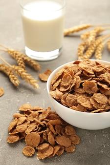 Chrupiące płatki kukurydziane i mleko na szarym tle. zdjęcie pionowe