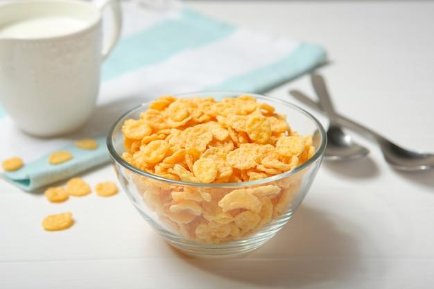 Chrupiące płatki kukurydziane z mlekiem na śniadanie na stole zbliżenie