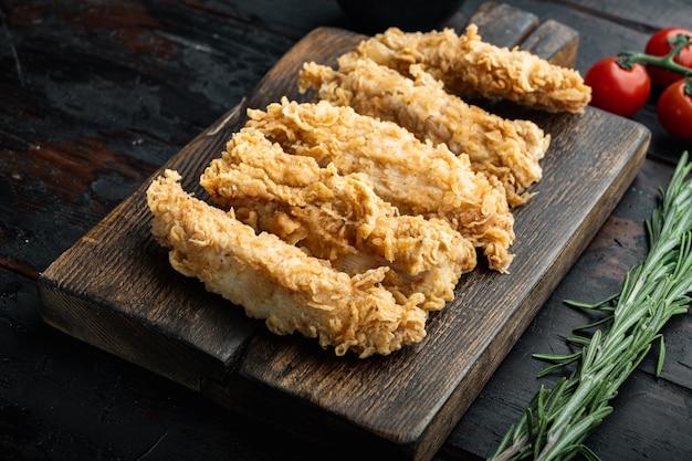 Chrupiące polędwiczki z kurczaka kawałki na ciemnym drewnianym stole.