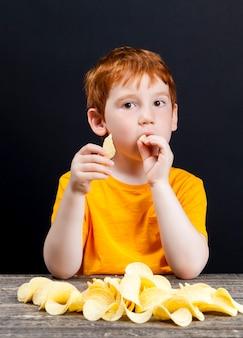 Chrupiące pyszne chipsy ziemniaczane, które zjada mały chłopiec z rudymi włosami, szkodliwe jedzenie, ale które dziecko naprawdę chce zjeść, chłopiec przy stole, zbliżenie