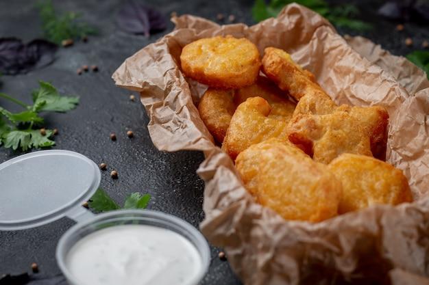 Chrupiące pyszne nuggetsy z kurczaka na ciemnym kamiennym tle z kremowym sosem. restauracja fast food. zdrowa opcja fast foodów.