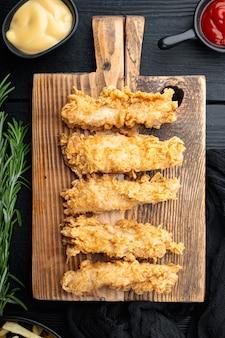 Chrupiące smażone kawałki pieczonego kurczaka na czarnym drewnianym stole, widok z góry.