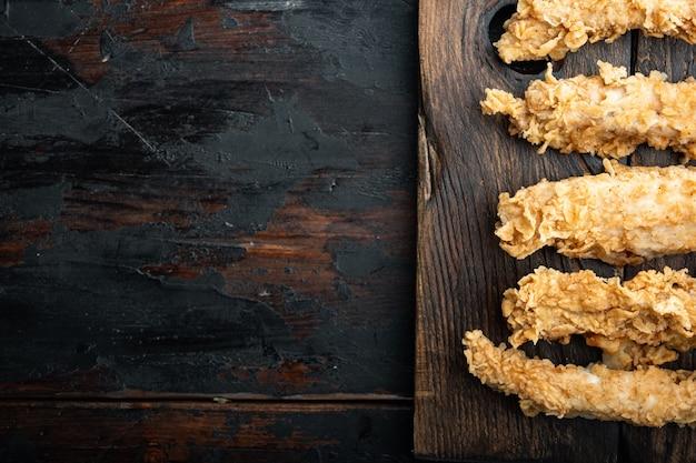 Chrupiące smażone kawałki piersi z kurczaka na starym ciemnym drewnianym stole