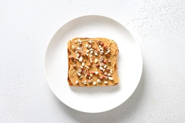 Chrupiące tosty z pastą orzechową w białej płytce na białym tle.