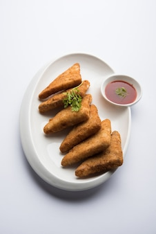 Chrupiące trójkąty ziemniaczane lub batata vada obsypane bułką tartą, a następnie smażone w głębokim tłuszczu. podawany z keczupem pomidorowym. selektywne skupienie