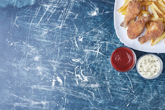 Chrupiące udka z kurczaka z paluszkami ziemniaczanymi i sosami.