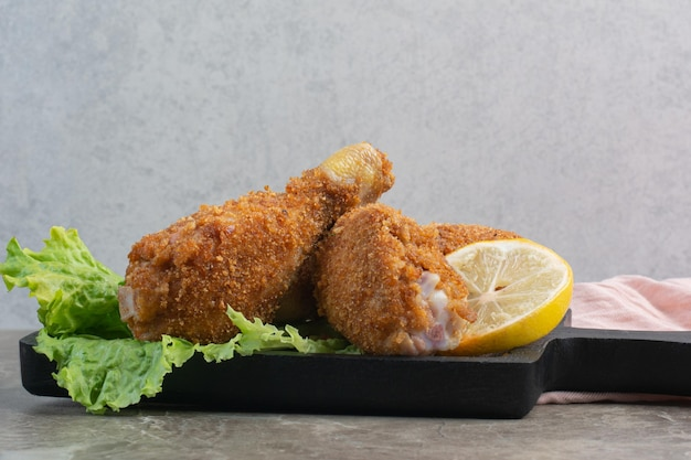 Chrupiące udka z kurczaka z sałatą i cytryną na ciemnej desce.
