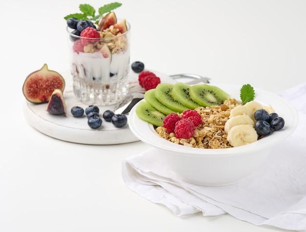 Chrupiące w białym okrągłym talerzu z malinami, kiwi, bananami. za szklanką z garnolą zamoczoną w jogurcie na białym stole. zdrowe śniadanie rano