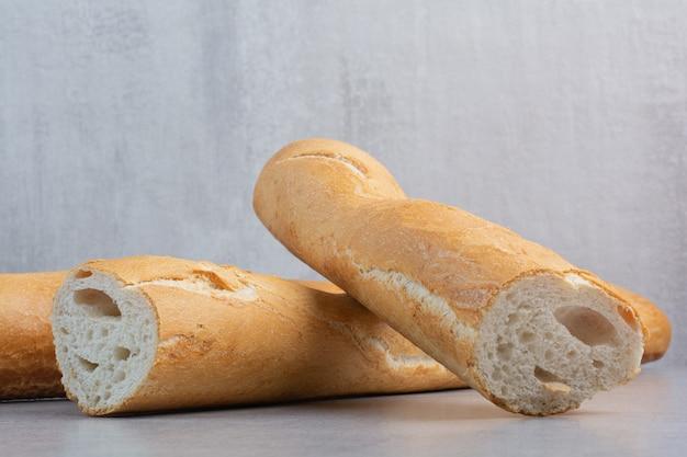 Chrupiący chleb bagietkowy na marmurowej powierzchni