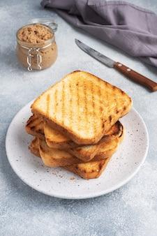 Chrupiący chleb tostowy do kanapek na talerzu na szarym betonowym stole. słoik pasztetu z kurczaka.