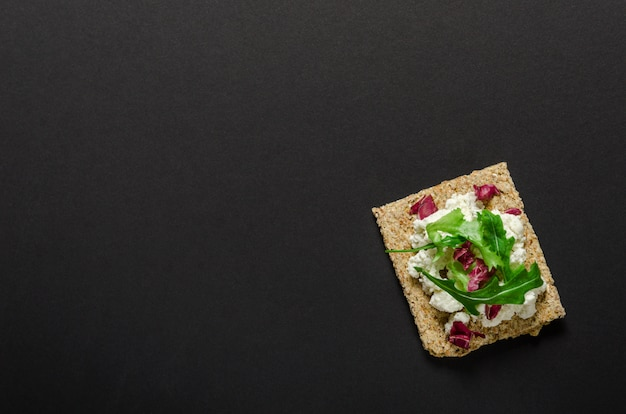 Chrupiący chleb z miękkim kremowym serem i ziele na czarnym tle. widok z góry.