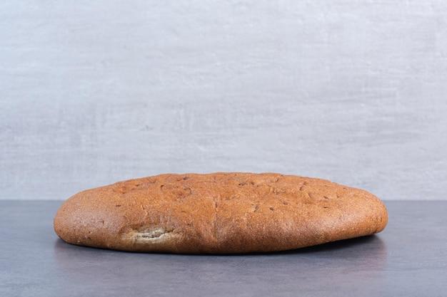 Chrupiący okrągły bochenek chleba na marmurowym tle. zdjęcie wysokiej jakości
