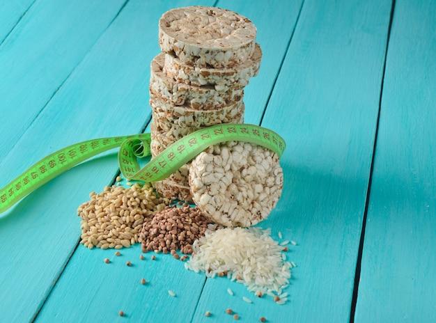 Chrupiący okrągły dietetyczny ryżowy gryczany chleb fitness zawinięty linijką na niebieskim drewnianym stole. jedzenie na odchudzanie.
