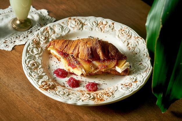 Chrupiący rogalik, delikatny serek śmietankowy, pieczony camembert, karmelizowana gruszka i konfitura różana w białym talerzu na drewnianym tle