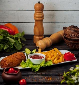 Chrupiący smażony filet z kurczaka podawany z frytkami i keczupem