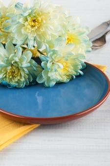 Chryzantema kwitnie na talerzu na drewnianym stole