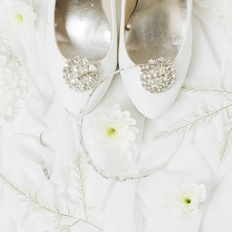 Chryzantema; obrączki ślubne; korona w pobliżu butów ślubnych na szaliku