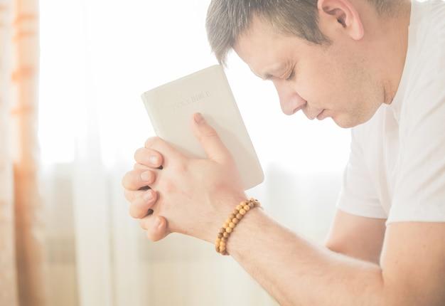 Chrześcijanin trzyma w rękach biblię. pojęcie wiary, duchowości i religii. modlitwa za modlitwę