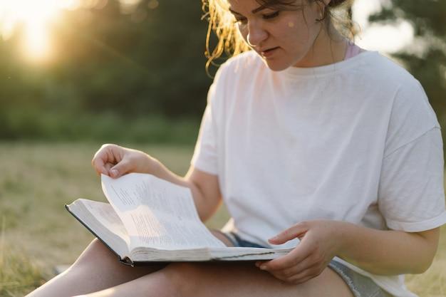 Chrześcijanka trzyma biblię w dłoniach czytając biblię na polu podczas pięknego zachodu słońca