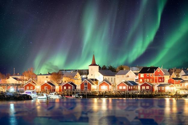 Chrześcijański kościół w wiosce rybackiej rozświetlony eksplozją zorzy polarnej w nocy