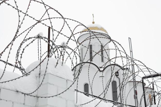 Chrześcijański kościół za płotem z drutu kolczastego w zimie.