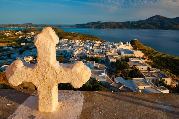 Chrześcijański krzyż i wioska plaka na wyspie milos nad czerwonymi kwiatami geranium o zachodzie słońca w grecji