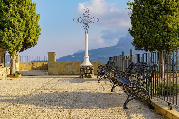 Chrześcijański krzyż w publicznym parku z żelaznymi ławkami do odpoczynku i punktem widokowym na góry.