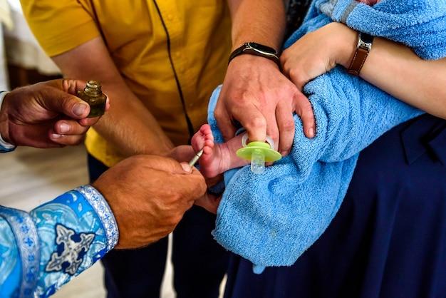 Chrześcijański obrzęd chrztu dziecka w kościele, kapłan namaszcza świat nogą małego dziecka
